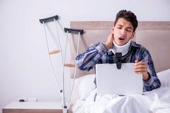 Den sårade mannen som direktanslutet hemma pratar via webcam i säng Royaltyfri Foto