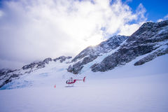 DEN SÖDRA ÖN, NYA SJÄLLAND MAY 24, 2017: Helikopter och pilot som väntar över snön för jägare i södra Westland ` s Arkivfoto