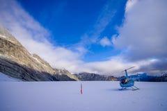DEN SÖDRA ÖN, NYA SJÄLLAND MAY 24, 2017: Helikopter och pilot som väntar över snön för jägare i södra Westland ` s Arkivbild