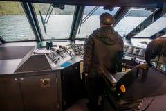 DEN SÖDRA ÖN, NYA SJÄLLAND MAY 25, 2017: Stäng sig upp av en färja med en kapten i kontrollera för kommandokabin Arkivbild