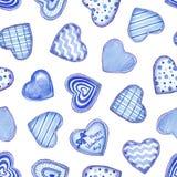 Den sömlösa modellen med blå hjärta för vattenfärgen formade kakor med glasyr på vit bakgrund royaltyfria foton