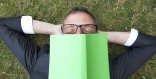 Den sömniga affärsmannen tröttade av läsning och att tycka om ett avbrott Royaltyfri Fotografi