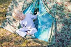 Den sömniga blonda pojken får ut ett tält i en morgon Fotografering för Bildbyråer