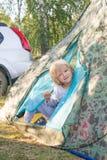 Den sömniga blonda pojken får ut ett tält i en morgon Royaltyfria Bilder