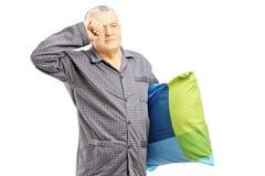 Den sömniga mitt åldrades mannen i pyjamas som rymmer en kudde Arkivbild