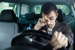 Den sömniga unga mannen gnider hans ögon med hans assistent Hans vänstra hand är på styrhjulet Han sitter på hans bil Vägsäkerhet fotografering för bildbyråer