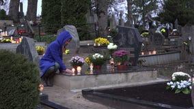 Den sörjande kvinnan sitter på grav på kyrkogården och ber med brännskadastearinljuset i händer 4K stock video