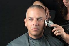 Den sörjande mannen får huvudet rakat för Fundraiser, ser till kameran arkivbild