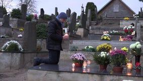Den sörjande mannen knäfaller på grav på kyrkogården och ber med brännskadastearinljuset i händer 4K arkivfilmer