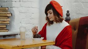 Den söta flickan av det Caucasian utseendet i en röd basker och att sitta i ett kafé och klipper en kaka på tabellen är en coctai arkivfilmer