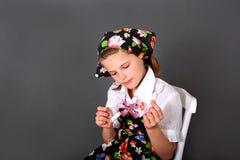 Den söta flickan broderar med ett visarsammanträde på en stol Royaltyfri Fotografi