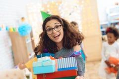 Den söta flickan i grön festlig hatt jublar på det enorma numret av gåvor på födelsedagen lycklig deltagare för födelsedag arkivfoto