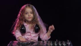 Den söta flickan med krullning spelar för dj-konsol Svart bakgrund stock video