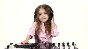 Den söta flickan med krullning spelar för dj-konsol Vit bakgrund arkivfilmer