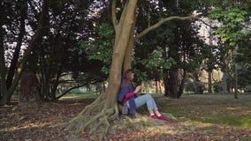 Den söta flickan med telefonen i hennes händer sitter under stort träd med vridning rotar att växa utanför arkivfilmer
