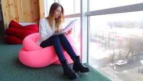 Den söta flickanyheternakorrespondentet skriver in text på minnestavlan med ark som in sitter i mjuk stol i kafé nära panorama- f stock video