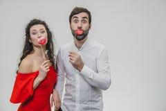 Den söta kvinnan och mannen rymmer rött fejkar kanter på en pinne Ha roligt frun är iklätt en röd klänning, en man i en vit skjor fotografering för bildbyråer