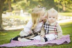 Den söta lilla flickan kysser henne behandla som ett barn brodern på parkera arkivbild