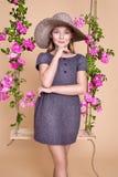 Den söta lilla flickan med en hatt på en gunga som dekorerades med, steg blommor Arkivfoton