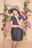 Den söta lilla flickan med en hatt på en gunga som dekorerades med, steg blommor Royaltyfri Bild