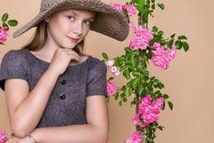 Den söta lilla flickan med en hatt på en gunga som dekorerades med, steg blommor Royaltyfri Fotografi