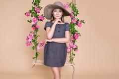 Den söta lilla flickan med en hatt på en gunga som dekorerades med, steg blommor Arkivbilder