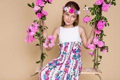 Den söta lilla flickan med en hatt på en gunga som dekorerades med, steg blommor Royaltyfria Bilder