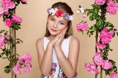 Den söta lilla flickan med en hatt på en gunga som dekorerades med, steg blommor Arkivfoto