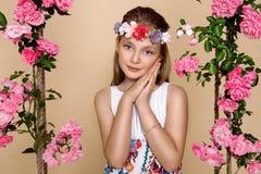 Den söta lilla flickan med en hatt på en gunga som dekorerades med, steg blommor Arkivbild