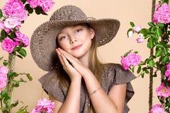 Den söta lilla flickan med en hatt på en gunga som dekorerades med, steg blommor Royaltyfria Foton