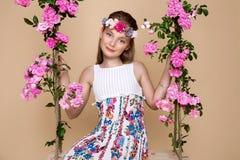 Den söta lilla flickan med en hatt på en gunga som dekorerades med, steg blommor Fotografering för Bildbyråer