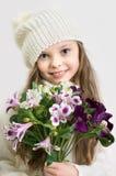 Den söta lilla flickan med hatten och blommor samlar ihop i händer Royaltyfri Bild