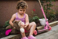 Den söta lilla flickan med lockigt hår är sitta och vila nära hennes rosa sparkcykel i borggården royaltyfria bilder