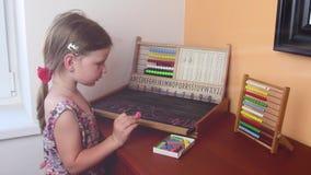 Den söta lilla flickan spelar med kulrammet och skriver på svart tavla med krita Förskole- begrepp, barndombegrepp toy stock video