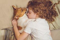 Den söta lockiga flickan och hunden sover i natt Arkivbild