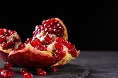 Den söta, nya och naturliga granatröttet för efterrätter och drycker på en svart bakgrund Den ljusa röda granatäpplet bröt ner arkivbilder