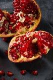 Den söta, nya och naturliga granatröttet för efterrätter och drycker på en svart bakgrund Den ljusa röda granatäpplet bröt ner royaltyfria foton