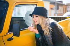 Den söta unga kvinnan applicerar röd läppstift som ser bilspegeln Royaltyfri Bild