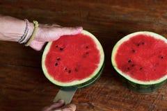 Den söta vatten-melon, mannen klipper enmelon, en kniv i enmelon royaltyfri fotografi