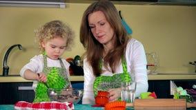 Den sött lite gulliga flickan lär från mamma hur man gör kakan i hem- kök stock video