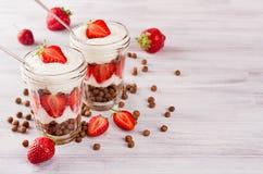 Den saftiga frukosten med choklad klumpa ihop sig den dekorerade skivade jordgubben för havreflingor på det vita wood brädet, kop Royaltyfri Foto