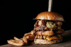 Den saftiga gigantiska hamburgaren med fransman steker på mörk bakgrund Royaltyfri Fotografi
