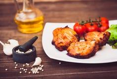 Den saftiga grillade grisköttfilén tjänade som med filialen för körsbärsröda tomater Arkivfoton