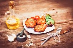 Den saftiga grillade grisköttfilén tjänade som med körsbärsröda tomater filial och grönsallat på den vita plattan Bakgrund: träbr Arkivbild