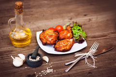 Den saftiga grillade grisköttfilén tjänade som med körsbärsröda tomater filial och grönsallat på den vita plattan Bakgrund: träbr Royaltyfria Foton