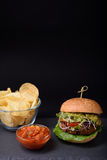 Den saftiga hamburgaren med salta potatischiper med ketchup kritiserar på brädet över svart bakgrund kopiera avstånd Arkivfoto