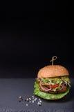 Den saftiga hemlagade hamburgaren med den grillade nötköttkotletten, peppar, sallad, tomaten, champinjoner, lök surved med peppar Royaltyfri Bild