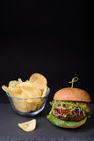 Den saftiga hemlagade hamburgaren med potatischiper kritiserar på brädet Arkivfoton