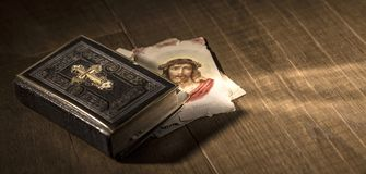 Den sakrala bibeln och helgedomkortet med Jesus Christ avbildar på ett skrivbord fotografering för bildbyråer