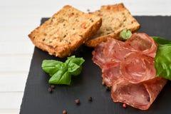 Den salami rökte korven skivar basilikasidor, pepparkorn och bröd royaltyfria foton